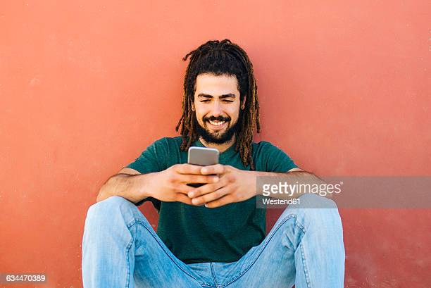 portrait of smiling young man with dreadlocks and beard looking at his smartphone in front of a reddish wall - rasta photos et images de collection