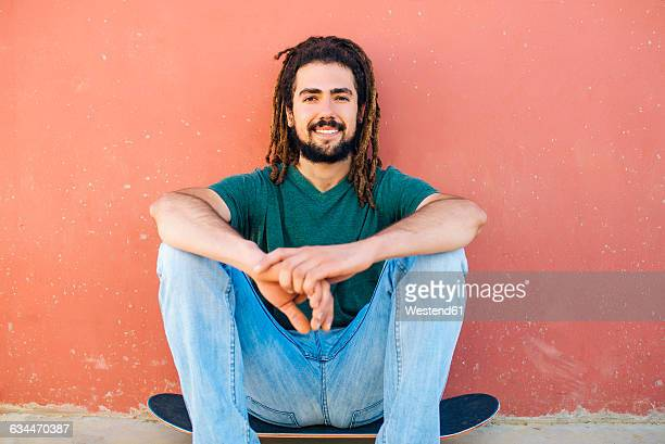 Portrait of smiling young man with dreadlocks and beard sitting on his skateboard in front of a reddish wall
