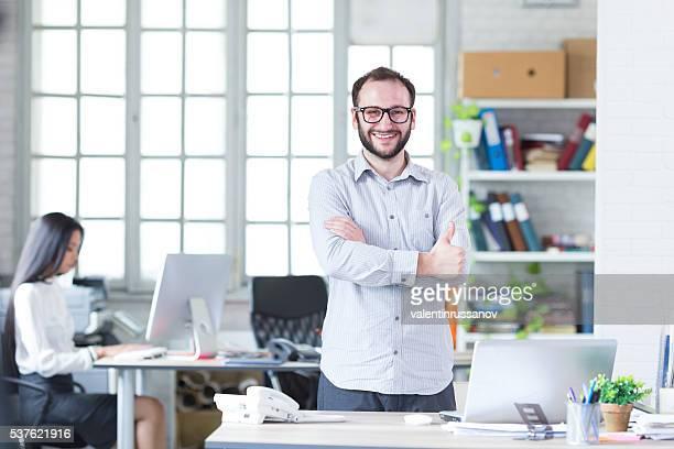 Porträt von lächelnd junger Mann mit brillen im Büro