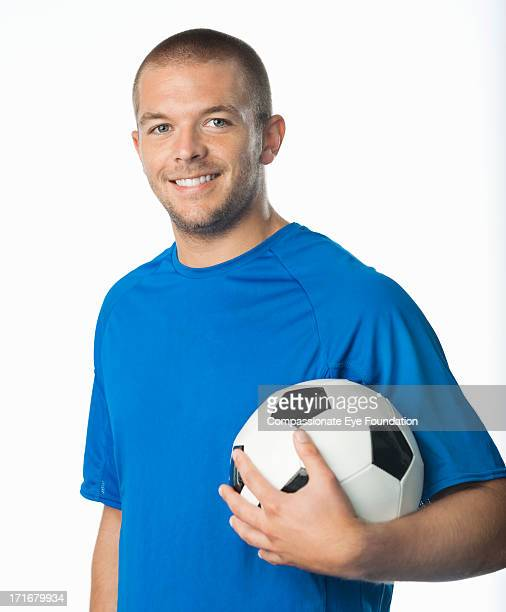 Portrait of smiling young man with football
