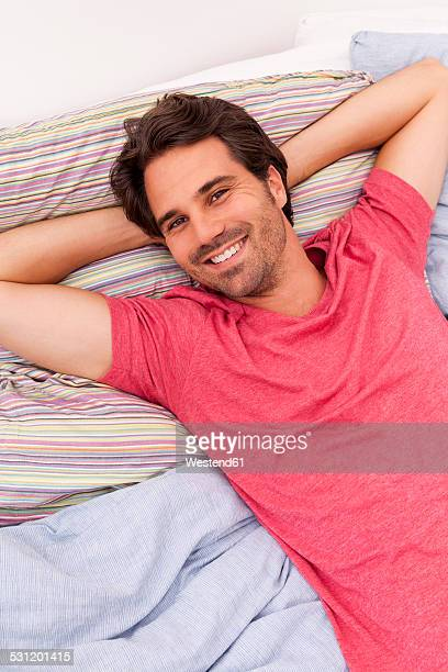 Portrait of smiling young man with hands behind head lying on his bed