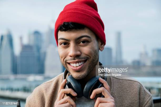 portrait of smiling young man with headphones - red hat stock pictures, royalty-free photos & images