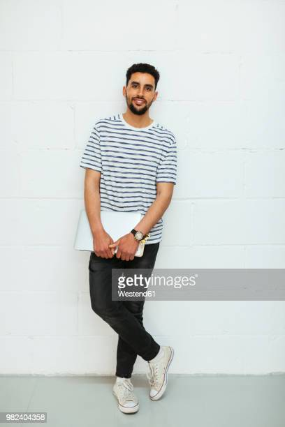 portrait of smiling young man with laptop standing at brick wall - north african ethnicity stock pictures, royalty-free photos & images