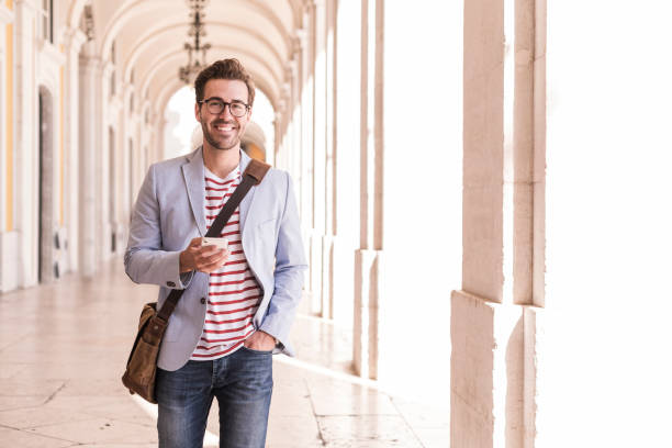 Portrait of smiling young man with smartphone in the city, Lisbon, Portugal