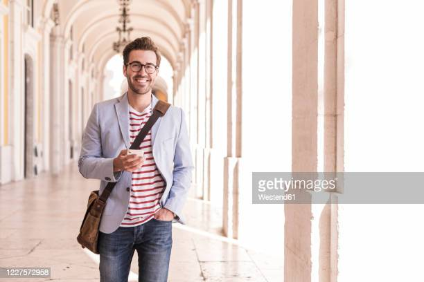 portrait of smiling young man with smartphone in the city, lisbon, portugal - crossbody bag stock pictures, royalty-free photos & images