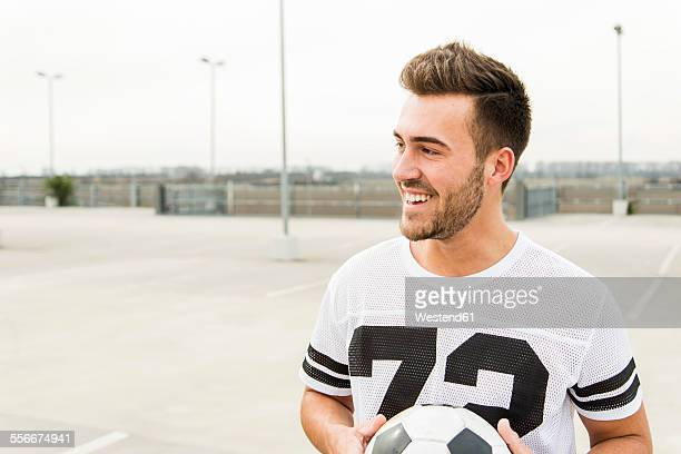 Portrait of smiling young man with soccer ball outdoors