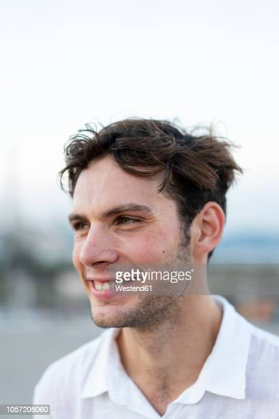 portrait of smiling young man with tousled hair outdoors - barba por fazer - fotografias e filmes do acervo