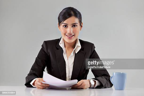 Portrait of smiling young news television host with coffee cup and paper