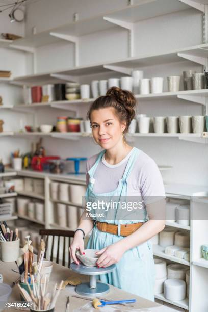 Portrait of smiling young potter molding shape on clay while standing by workbench at store