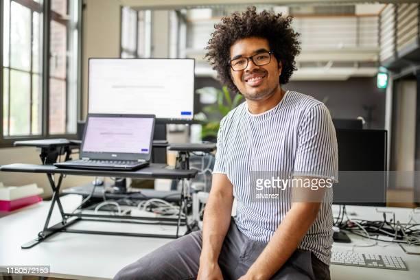 portrait de jeune professionnel souriant s'asseyant au bureau - 25 29 ans photos et images de collection