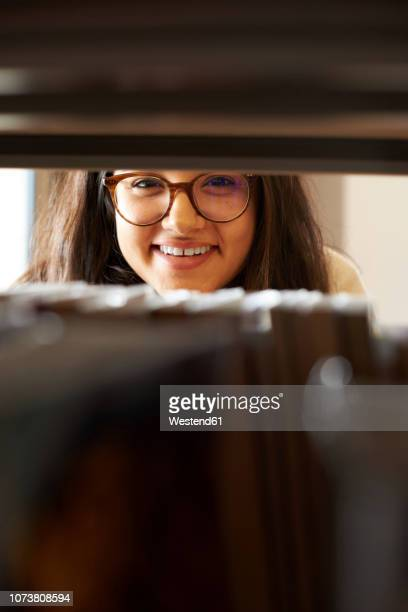 portrait of smiling young student looking through bookshelf in the library - looking through an object stock pictures, royalty-free photos & images