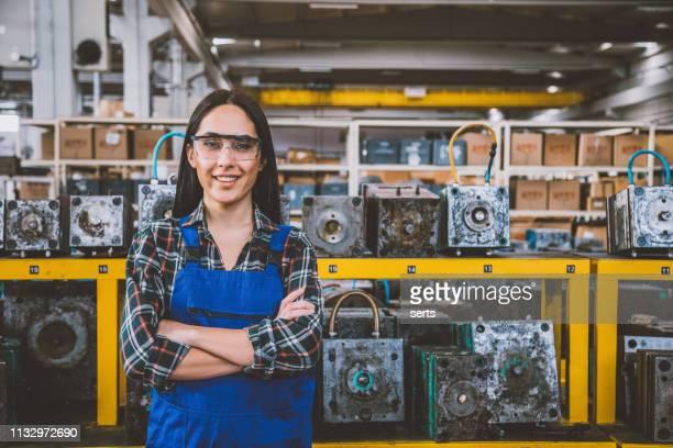 porträt der lächelnden jungen technikerin in fabrik - handwerker stock-fotos und bilder
