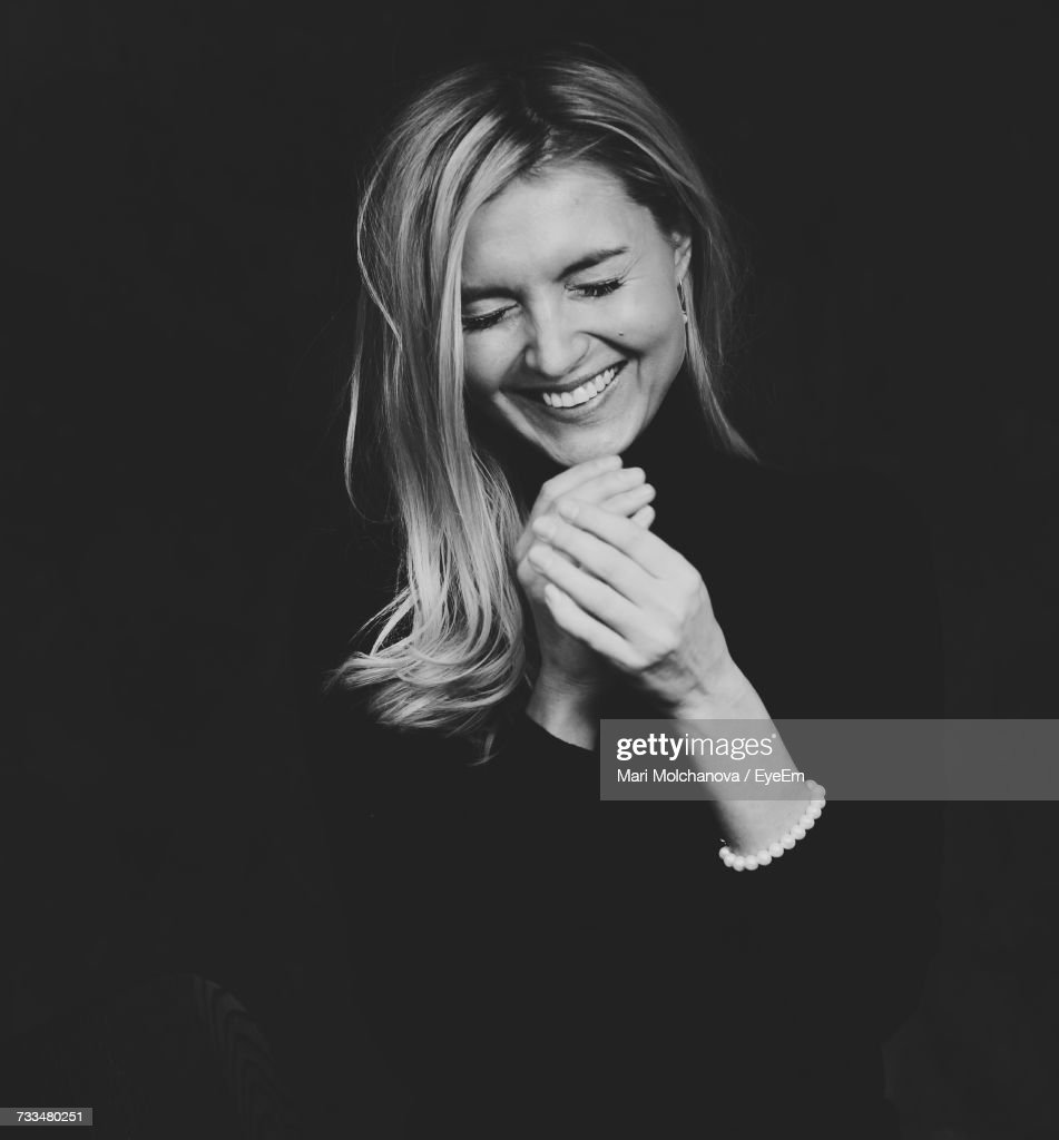 Portrait Of Smiling Young Woman Against Black Background : Stock Photo