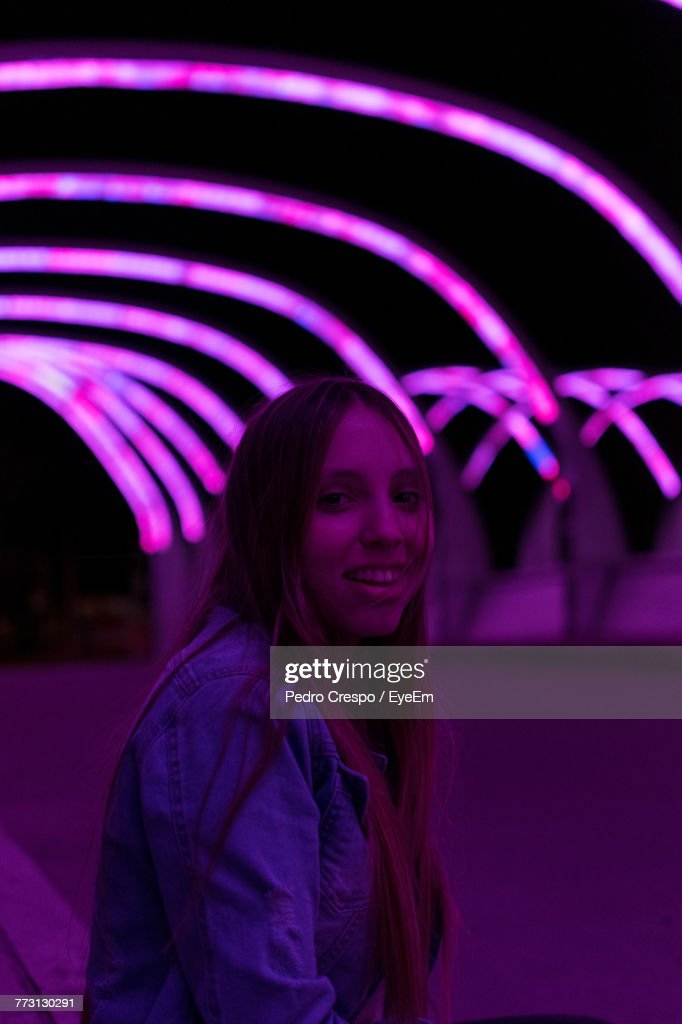 Portrait Of Smiling Young Woman Against Illuminated Purple Lighting : Photo