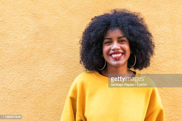 portrait of smiling young woman against standing yellow wall - nose piercing stock pictures, royalty-free photos & images