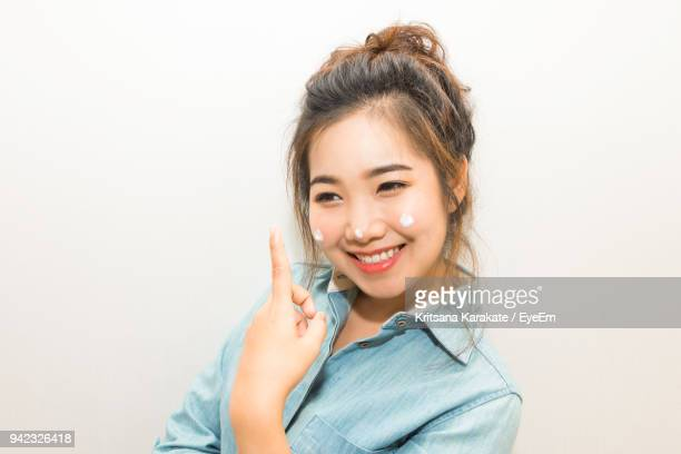 Portrait Of Smiling Young Woman Applying Moisturizer Against White Background