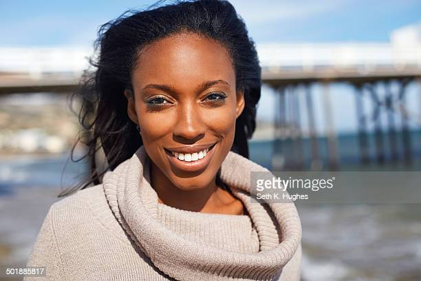 Portrait of smiling young woman at beach, Malibu, California, USA