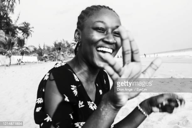 portrait of smiling young woman at beach - côte d'ivoire stock pictures, royalty-free photos & images