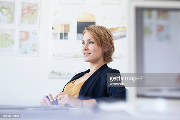 portrait of smiling young woman at her desk in a creative office - variable schärfentiefe stock-fotos und bilder