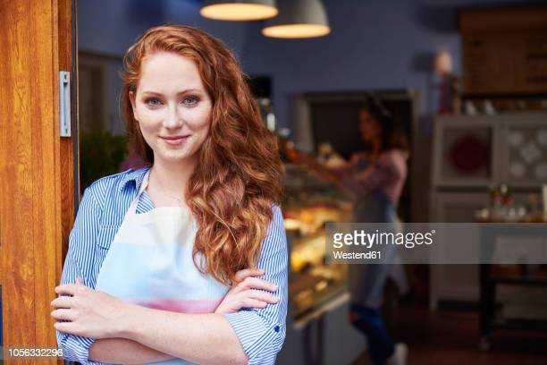 portrait of smiling young woman at the entrance of a bakery - redhead stock pictures, royalty-free photos & images