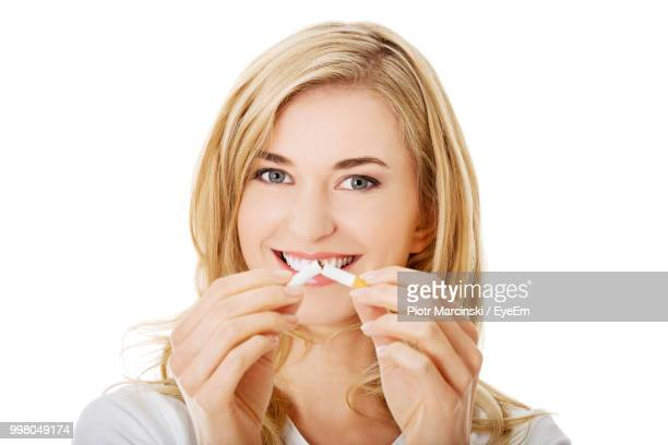 Portrait Of Smiling Young Woman Breaking Cigarette Against White Background
