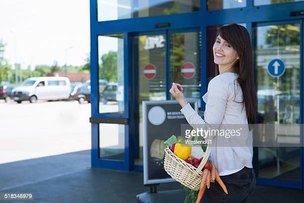 Portrait of smiling young woman carrying basket with fresh vegetables