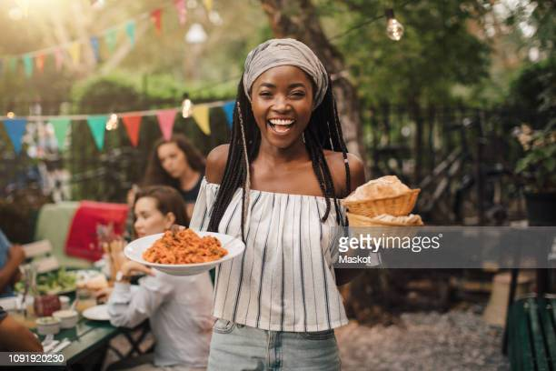 portrait of smiling young woman carrying food while standing in backyard during garden party - ready to eat stock pictures, royalty-free photos & images