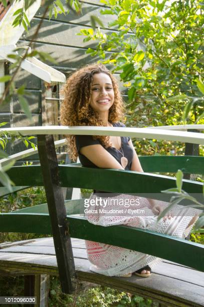 Portrait Of Smiling Young Woman Crouching On Footbridge At Park