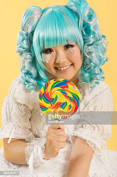 portrait of smiling young woman dressed as a doll holding lollipop over yellow background - candy dolls fotografías e imágenes de stock