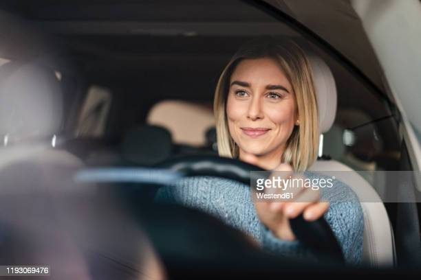 portrait of smiling young woman driving a car - auto stockfoto's en -beelden