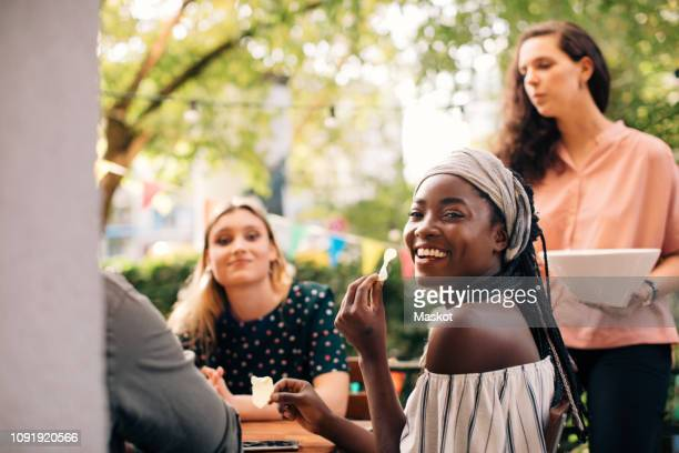 portrait of smiling young woman eating snacks with friends in balcony - snack stock pictures, royalty-free photos & images