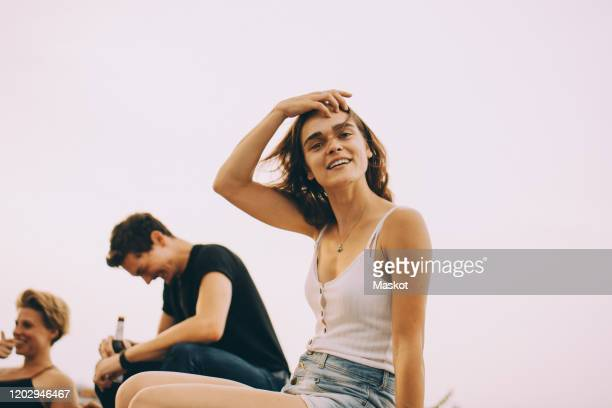 portrait of smiling young woman enjoying party with friends on terrace during windy day - 25 29 jahre stock-fotos und bilder