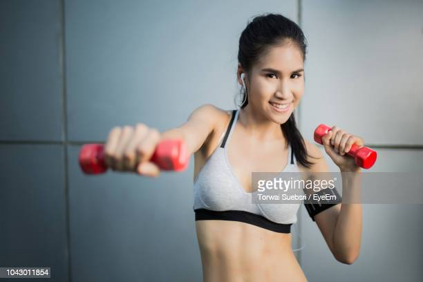 portrait of smiling young woman exercising against wall - torwai stock pictures, royalty-free photos & images