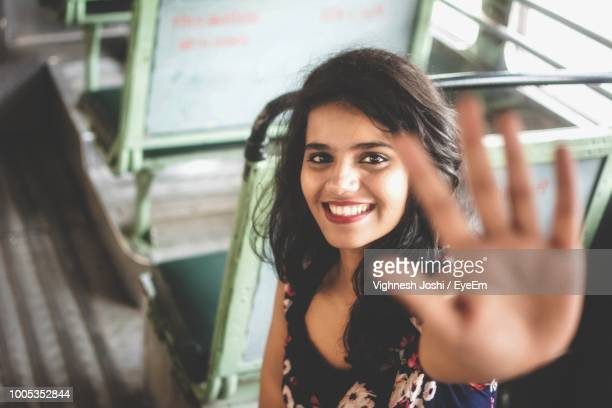 portrait of smiling young woman gesturing while sitting in bus - femme indienne photos et images de collection