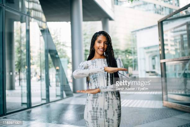portrait of smiling young woman gesturing while standing on floor - equality stock pictures, royalty-free photos & images