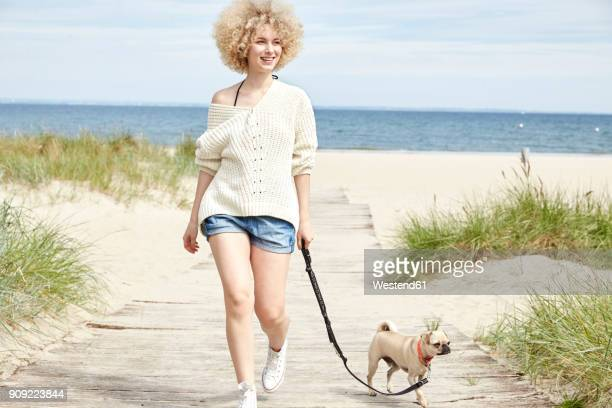 portrait of smiling young woman going walkies with her dog on the beach - アフロ ストックフォトと画像