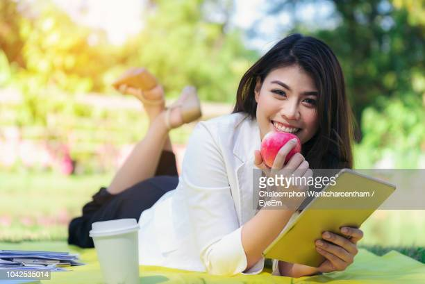 Portrait Of Smiling Young Woman Holding Apple And Tablet At Park