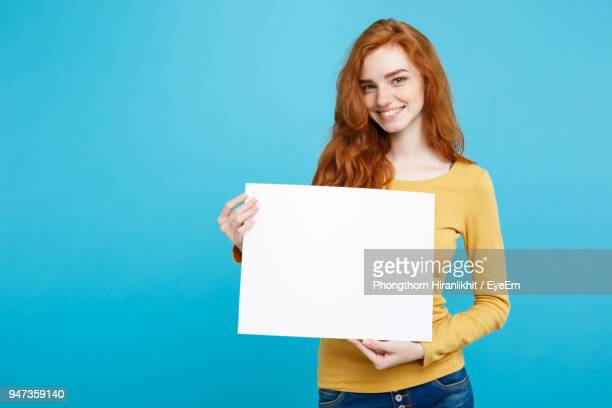 portrait of smiling young woman holding blank placard against blue background - cogiendo fotografías e imágenes de stock