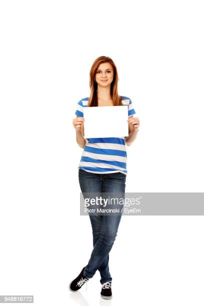 portrait of smiling young woman holding blank placard against white background - プラカード ストックフォトと画像