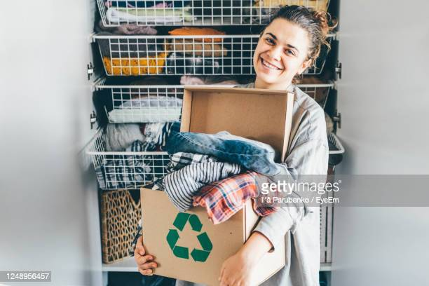 portrait of smiling young woman holding box - clothing stock pictures, royalty-free photos & images