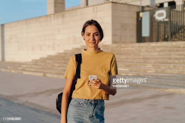 portrait of smiling young woman holding cell phone outdoors - donne giovani foto e immagini stock