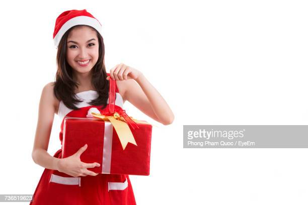 Portrait Of Smiling Young Woman Holding Christmas Present Against White Background