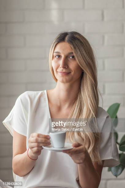portrait of smiling young woman holding coffee at home - marija mauer stock-fotos und bilder