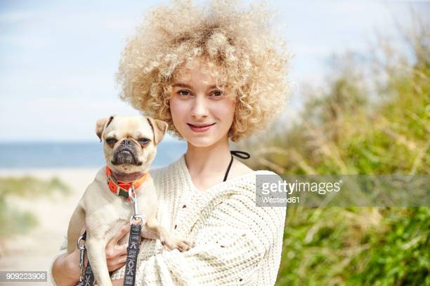 portrait of smiling young woman holding dog on her arms - gelockt stock-fotos und bilder