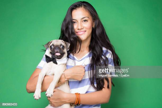 Portrait Of Smiling Young Woman Holding Dog Over Green Background