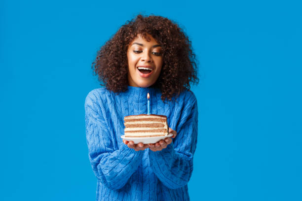 Portrait of smiling young woman holding donut against blue background