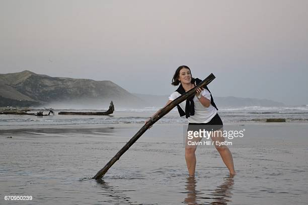 Portrait Of Smiling Young Woman Holding Driftwood At Beach