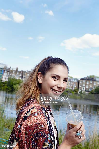 Portrait of smiling young woman holding drink