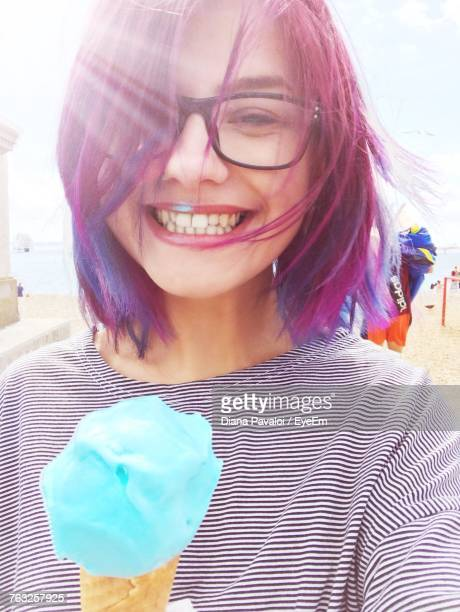 Portrait Of Smiling Young Woman Holding Ice Cream