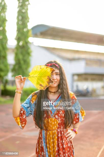 portrait of smiling young woman holding leaf over face while standing on land - anuwat somhan stock photos and pictures